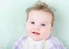 Baby in einem purpurroten Kleid, das auf einem Grün liegt, strickte Decke Lizenzfreie Stockfotos