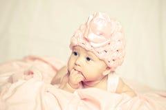 Baby in einem rosafarbenen Hut Stockbilder