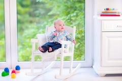 Baby in einem Schaukelstuhl Stockfotos