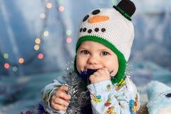Baby in einem Weihnachtsschneemann, der Feiertagsdekorationslametta hält, Lizenzfreie Stockfotos