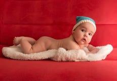 Baby in einer blauen Kappe, liegend auf einer weißen Haut Stockfotografie