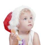 Baby in einer roten Schutzkappe des neuen Jahres Stockfotografie