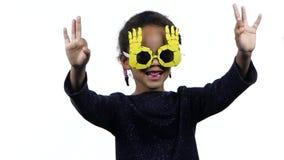 Baby eines Afroamerikanermädchentanzens in den lustigen Gläsern Weißer Hintergrund Langsame Bewegung stock footage