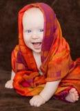 Baby eingewickelt in einem orange Schal Stockbild