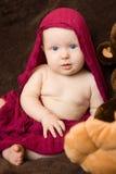 Baby eingewickelt in einem roten Schal Stockfotos