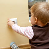 Baby at electric socket. Baby sitting at electric socket, touching it stock photo