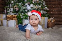 Baby in elf costume playing with old wooden train and soft toy bears under the Christmas tree, vintage. stock image