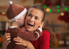 Baby embracing happy mother and in christmas decorated kitchen Stock Images