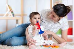 Baby en haar muzikaal speelgoed van het moederspel stock fotografie