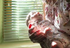Baby en mamma aan het venster Stock Fotografie