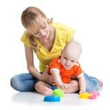 Baby en moeder het spelen samen met kleurrijk speelgoed stock afbeelding