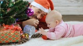 Baby en papa onder de Kerstboom stock video