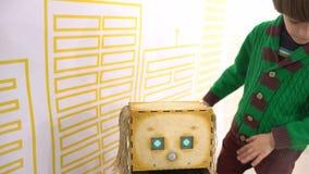 Baby en robot Kind en robot: een nieuwsgierige jongen bij een tentoonstelling van robots Modern speelgoed Kinderen en de toekomst stock video