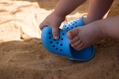 baby&en x27; s lägger benen på ryggen i strandsanden, blått bläddrar misslyckanden och en leksakskyffel, lek i sandlådan arkivfoton