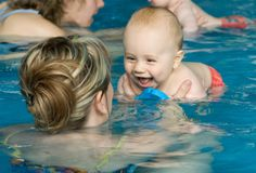 Baby enjoying first swim. A happy baby enjoying first swim with mother stock image