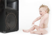 Baby enjoying sound in front of loudspeaker. Little baby with mohawk hair style enjoying music and laughing Stock Images