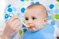 Baby enjoys feeding Stock Image