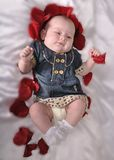Baby with an entourage of red petals rose Royalty Free Stock Photos