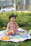 Baby entspannen sich auf Gras mit Spielwaren Stockfotografie