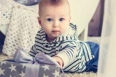 Baby erreicht zu seinem Geschenk lizenzfreie stockfotografie