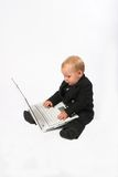 Baby executive. Young child in suit working on a laptop computer, isolated Royalty Free Stock Images