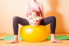 Baby exercises on fitball. Caring mother doing sport exercises with her baby on fitball Royalty Free Stock Image