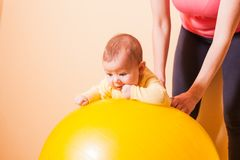 Baby exercises on fitball. Caring mother doing sport exercises with her baby on fitball Royalty Free Stock Photography