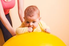 Baby exercises on fitball. Caring mother doing sport exercises with her baby on fitball Stock Photography