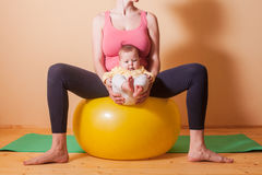 Baby exercises on the fitball. Caring mother doing sport exercises with her baby on fitball Royalty Free Stock Images