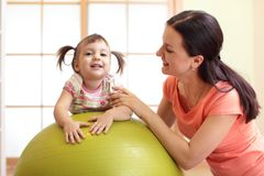 Baby exercises on the fitball. Mom with kid doing yoga or fitness Stock Photo