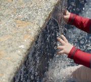 A baby explores a fountain Stock Photo