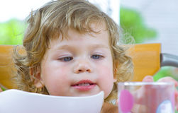 Baby face. Portrait of nice curled baby in lunch time Stock Photo