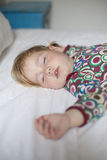Baby face sleeping on bed. Blonde caucasian baby face nineteen month age with colored shirt sleeping on white sheets king bed royalty free stock image
