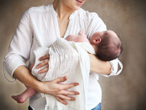 Baby falling asleep in the arms of her mother Stock Photos