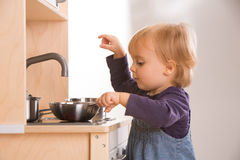Baby family girl daughter play cooking in toy kitchen.  Royalty Free Stock Image