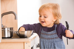 Baby family girl daughter play cooking in toy kitchen.  Royalty Free Stock Photos
