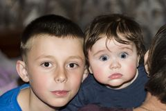 The brat hugs a sister on her grandmother`s shoulder. The baby fascinates us with her look and smile Stock Photos