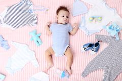 Baby with fashion clothes. Cute baby with fashion clothes and toys lying on pink bed royalty free stock photography