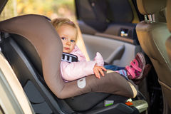 Baby fastened in car seat royalty free stock photo