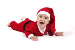 Baby in Father Christmas suit. Smiling baby boy lying on floor dressed in Father Christmas outfit, isolated on white background Stock Photography