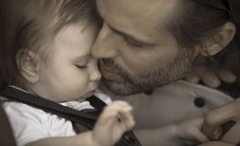 Baby Father Kiss. A father is kissing gently his young baby boy on the nose. Aged photo effect Royalty Free Stock Image