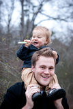 Baby on father's shoulders with toothbrush. Stock Photo