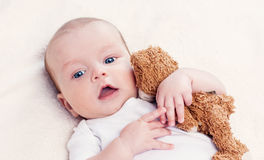 Baby with a favorite toy. Supine Royalty Free Stock Images
