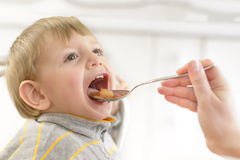 Baby Fed by his Mom. Baby boy fed by his mom at home stock photos