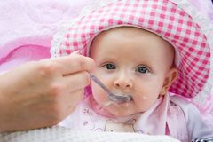 Baby is fed from a spoon Royalty Free Stock Photos