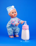 Baby feeding bottle. On blue background with toy baby royalty free stock image