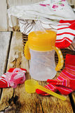 Baby feeding bottle. And baby clothes in a basket on an old wooden table. child care Royalty Free Stock Images