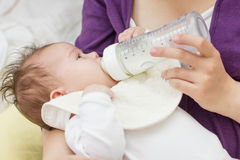 Baby Feeding Bottle. Mother feeding baby with milk from a bottle Stock Images