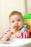 Baby feeding herself Stock Image