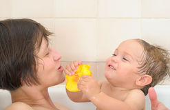 Baby feeding his mama peach. One year old baby with curly wet hair gives his mama peach fruit Stock Photography